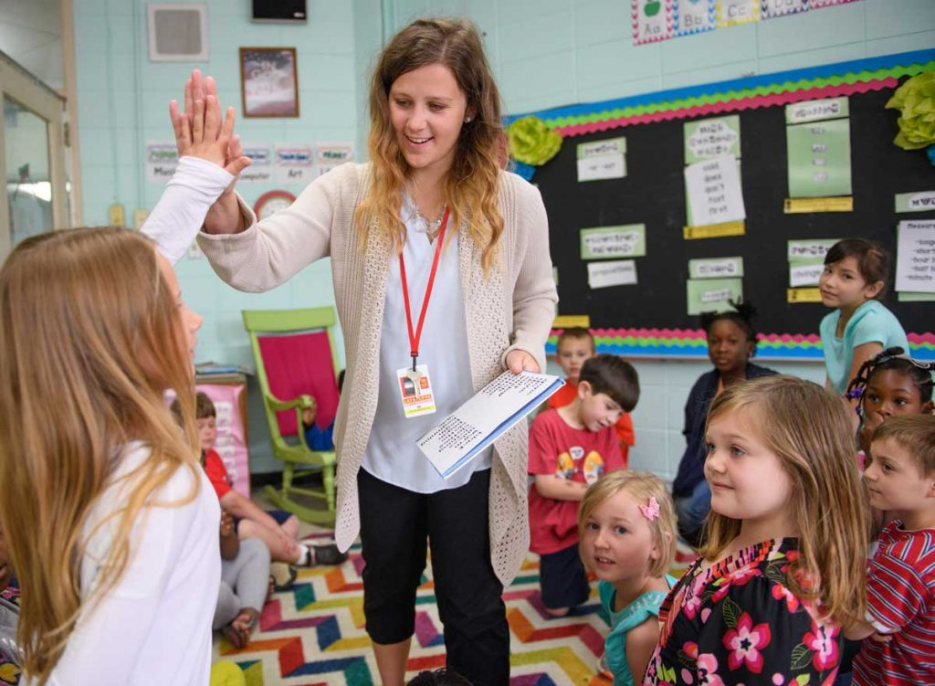 Teacher high-fiving young students